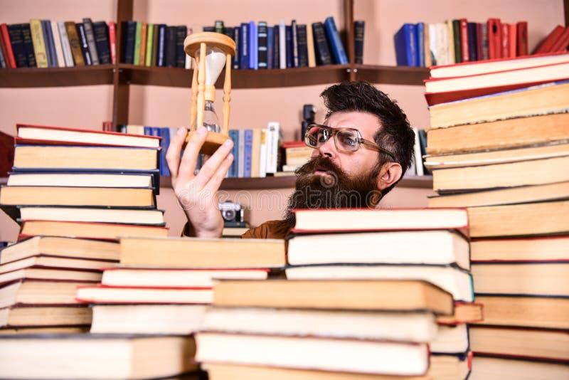 De mens op nadenkend gezicht houdt zandloper terwijl het bestuderen, boekenrekken op achtergrond De mens, wetenschapper in glazen royalty-vrije stock afbeeldingen