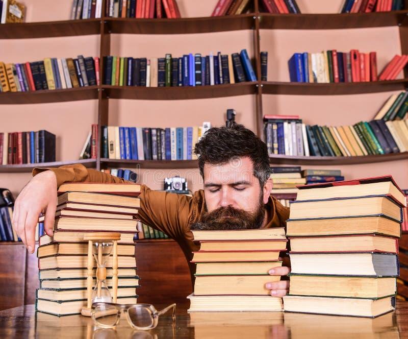De mens op slaapgezicht legt tussen stapels van boeken, valt in slaap terwijl het bestuderen in bibliotheek, boekenrekken op acht royalty-vrije stock afbeelding