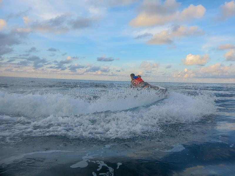 De mens op straalskidraaien met veel bespat De jongen die van de tienerleeftijd op waterautoped ski?en Jonge mens op waterscooter stock afbeelding