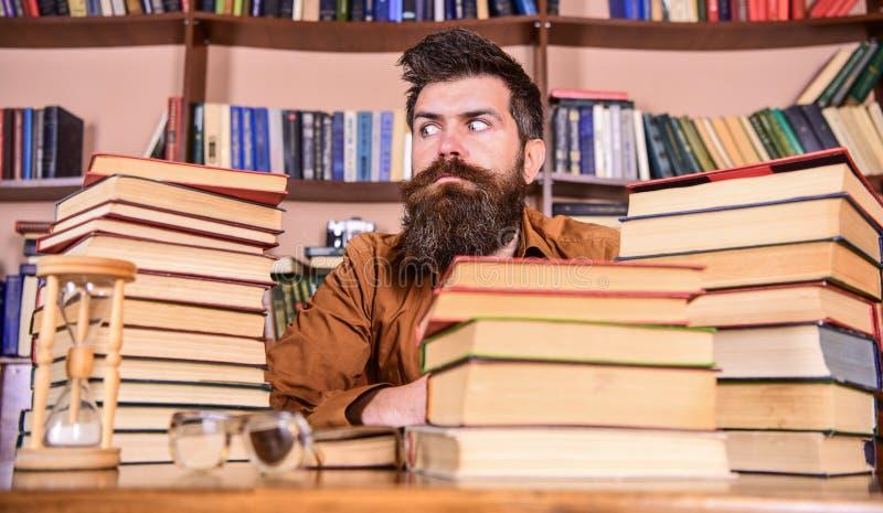 De mens op strikt gezicht zit tussen stapels van boeken, terwijl het bestuderen in bibliotheek, boekenrekken op achtergrond Boeke royalty-vrije stock afbeelding