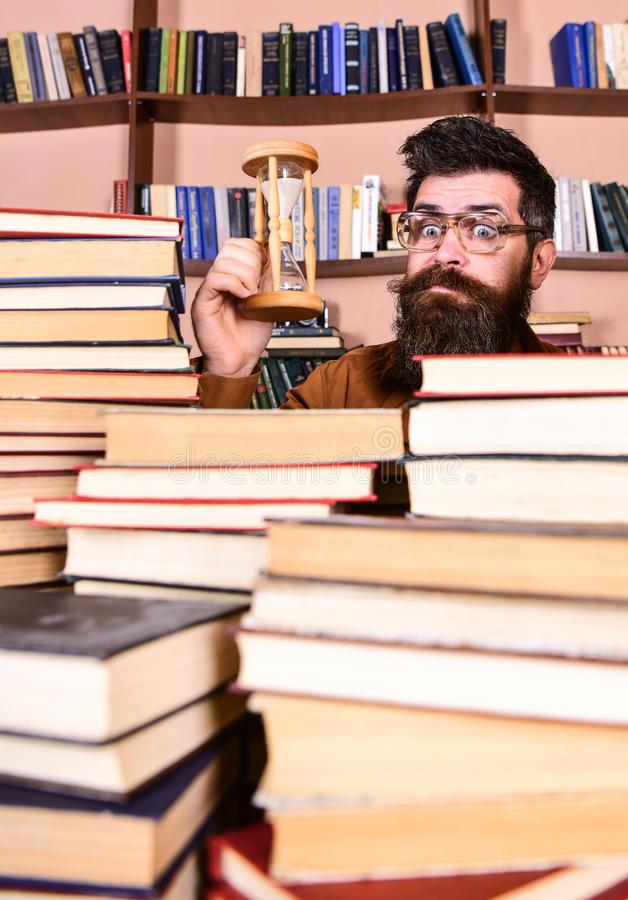 De mens op verrast gezicht houdt zandloper terwijl het bestuderen, boekenrekken op achtergrond Het Concept van de tijdstroom Lera royalty-vrije stock foto's