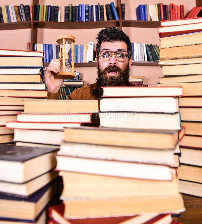 De mens op verrast gezicht houdt zandloper terwijl het bestuderen, boekenrekken op achtergrond Het Concept van de tijdstroom Mens stock afbeelding