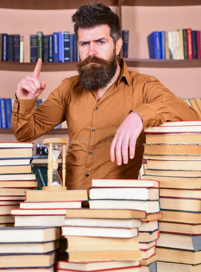 De mens op zeker gezicht bevindt zich tussen stapels van boeken, terwijl het bestuderen in bibliotheek, boekenrekken op achtergro royalty-vrije stock afbeeldingen