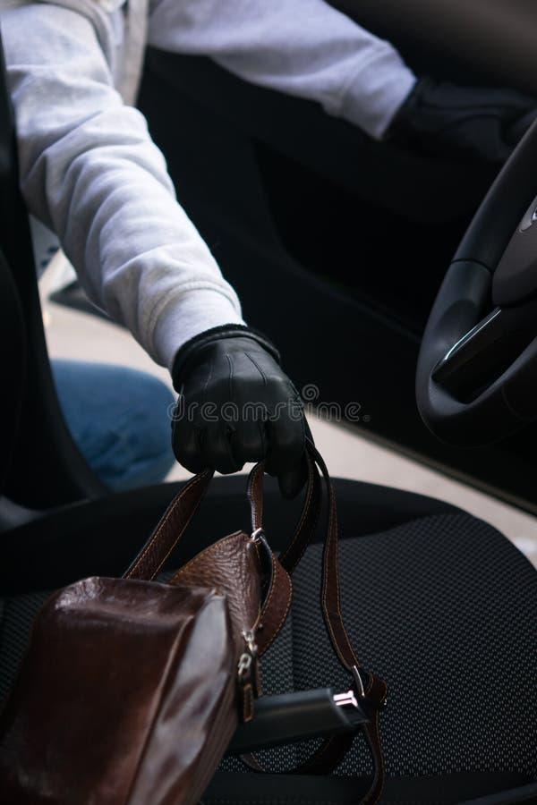 De mens opende de deur van de auto en wil iemand anders dingen stelen stock afbeelding