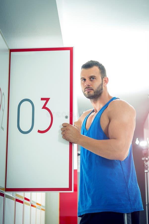 De mens opent kastdeur in gymnastiek stock afbeelding