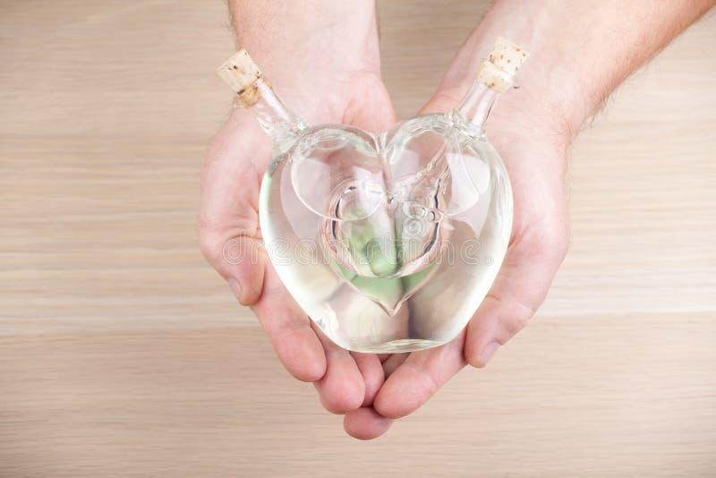 De mens overhandigt glas groen hartparfum royalty-vrije stock foto's