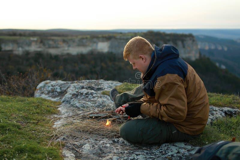 De mens probeert om een brand met een vuursteen te maken royalty-vrije stock afbeelding