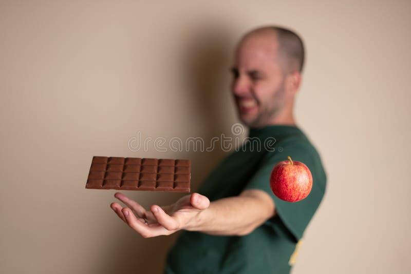 De mens probeert om een chocoladereep te grijpen met één hand en het negeren van de gezonde optie stock foto