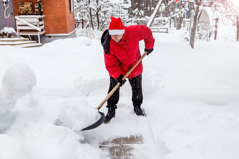 De mens in rood benedenjasje en rode hoed van de Kerstman ontruimt sneeuw in binnenplaats Ontruimt sneeuwbanken op weg aan huis I royalty-vrije stock afbeeldingen