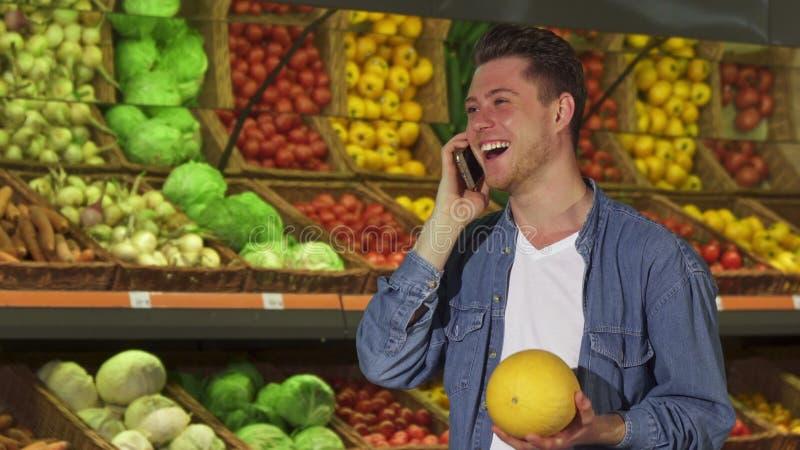 De mens ruikt meloen bij de supermarkt stock afbeelding