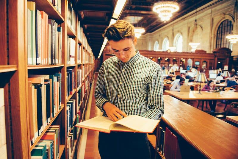 De mens in de ruimte van de bibliotheeklezing nam het boek van de plank en de lezing stock afbeeldingen