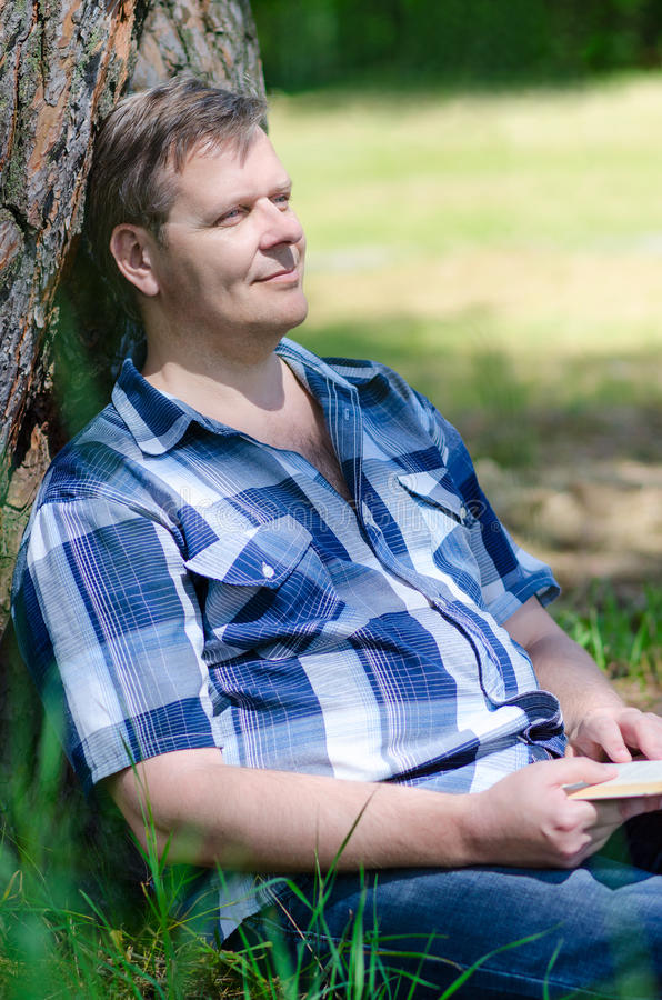 De mens rust met boek in handen op gazon royalty-vrije stock foto