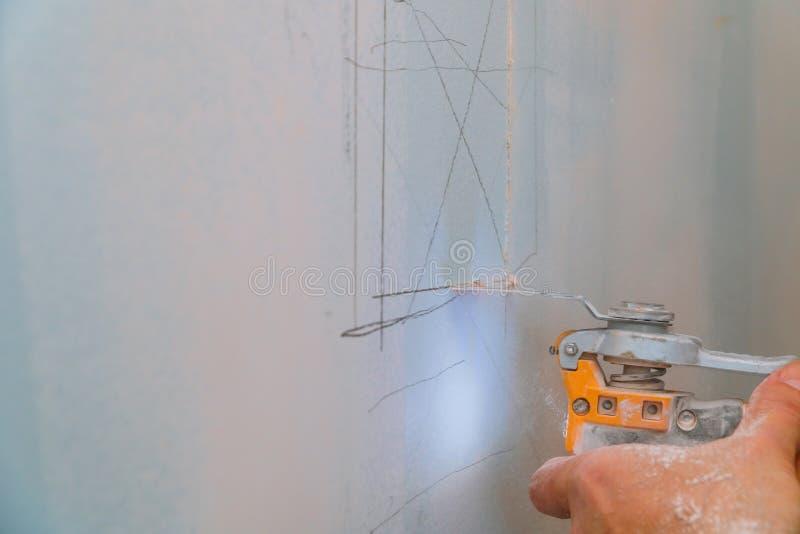 De mens is scherpe gipsraad binnen met elektro de werkenvernieuwing van de messenreparatie in restauratie Drywall paneel stock foto