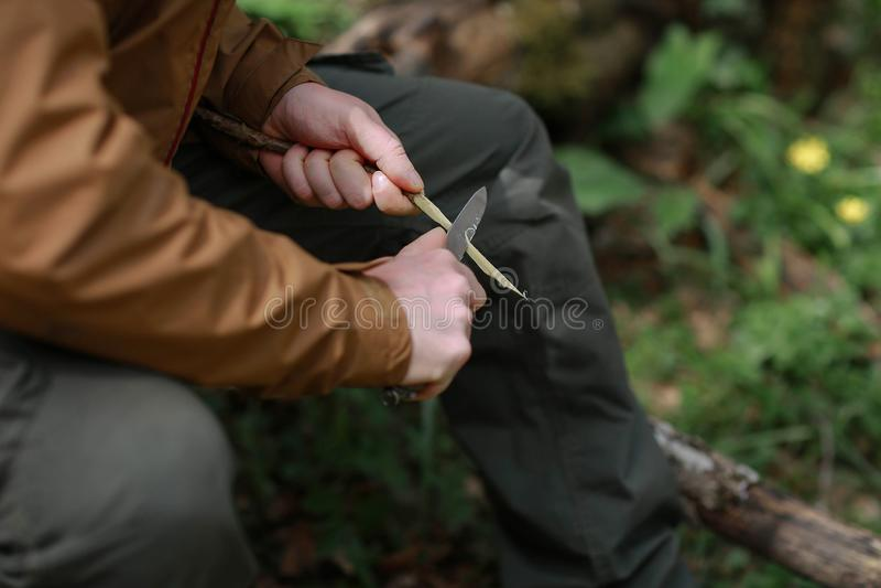 De mens scherpt een tak met een mes stock afbeelding