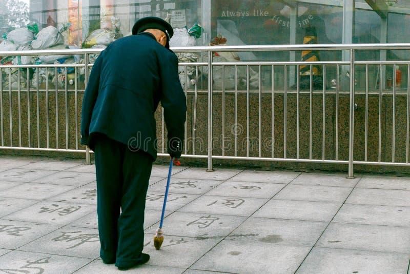 De mens schildert Chinese karakters stock foto's