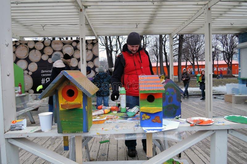 De mens schildert huizen voor vogels stock afbeeldingen