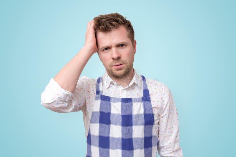 De mens in schort die kijkt gaand ernstig besluit wat nemen voor diner te koken in verwarring hebben gebracht stock fotografie
