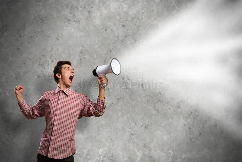 De mens schreeuwt in een megafoon royalty-vrije stock foto's