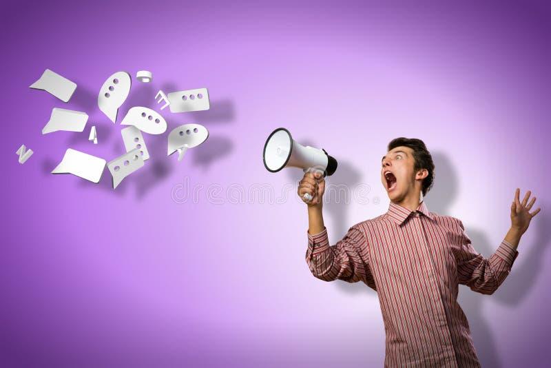 De mens schreeuwt in een megafoon stock foto