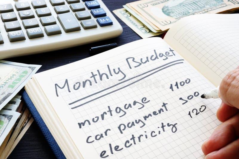 De mens schrijft Maandelijks Begrotingsplan Huisfinanciën stock fotografie