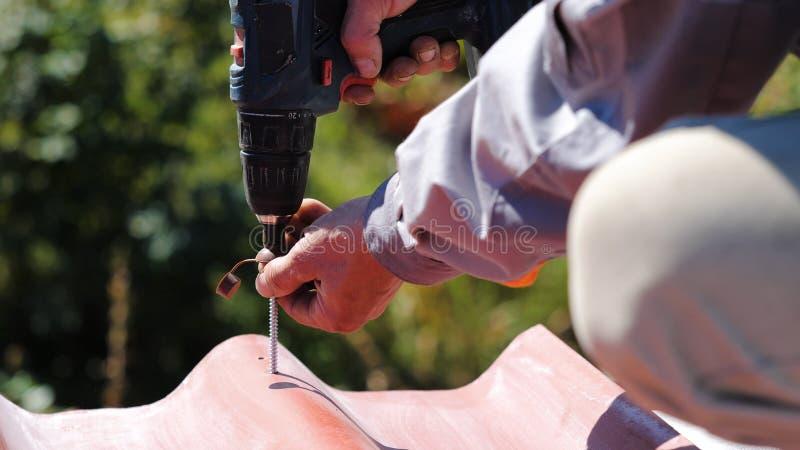 De mens schroeft een schroef in het dak Voorraadlengte De professionele arbeider werkt langs aan installatie van een dak van een  stock foto's