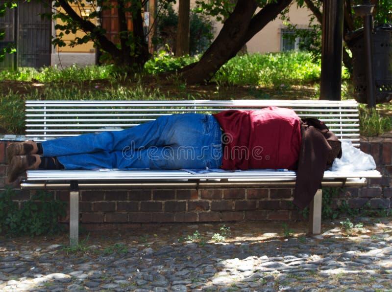 De mens slaapt op de bank van een park van Bologna, Italië stock fotografie