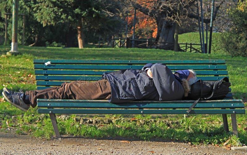 De mens slaapt in park van Milaan royalty-vrije stock afbeeldingen