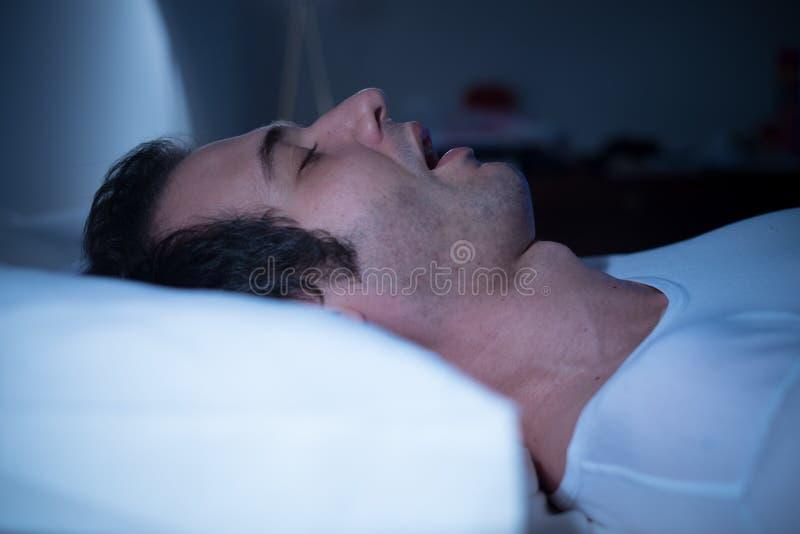 De mens slaapt in zijn bed royalty-vrije stock afbeelding