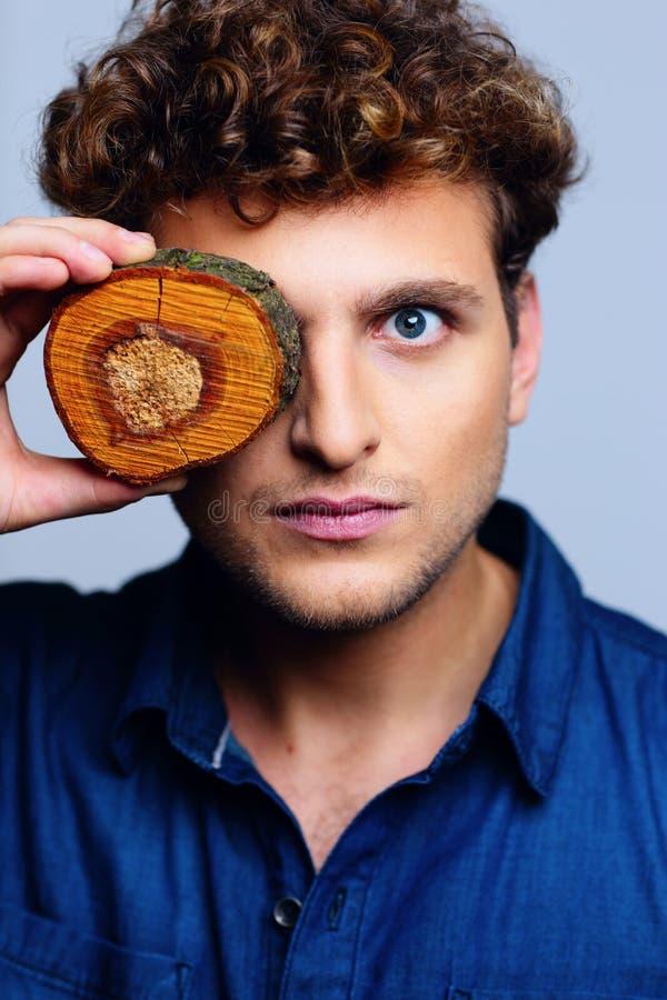 De mens sloot zijn oog door houten cirkels stock foto's