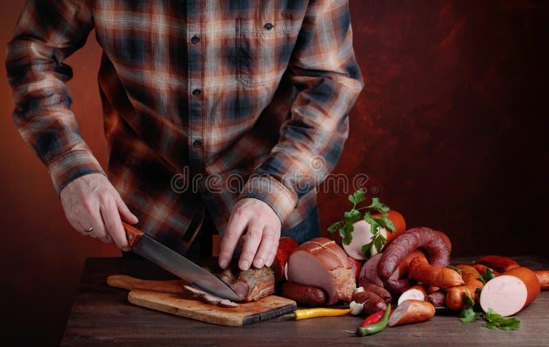 De mens snijdt diverse worsten en gerookt vlees stock fotografie