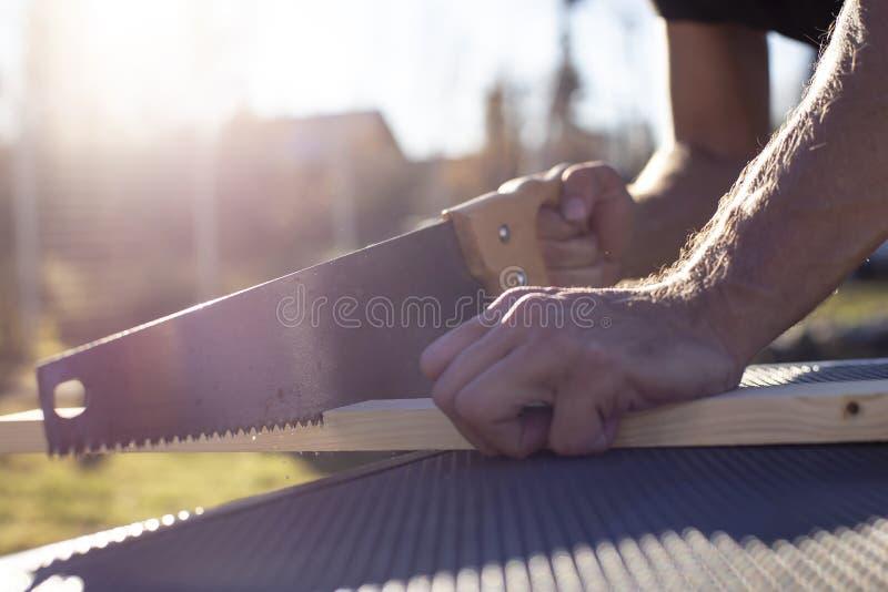 De mens snijdt een houten product met een timmerwerkhandzaag, in de zonneschijn op een warme de zomerdag royalty-vrije stock afbeelding