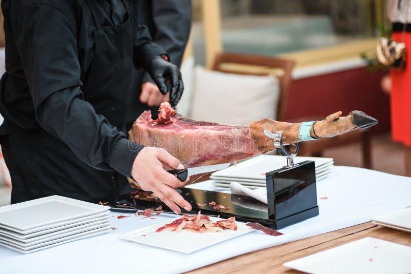De mens snijdt hamon stock afbeelding