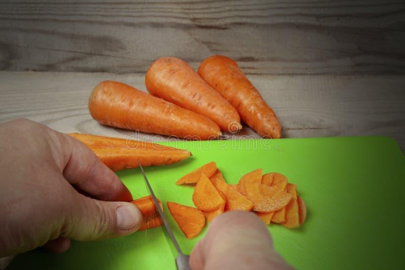 De mens snijdt wortelen op de keukenraad stock afbeelding