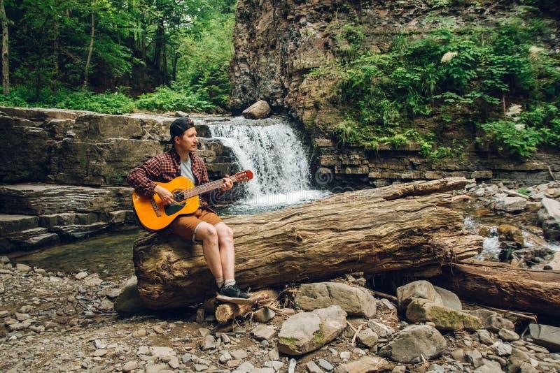 De mens speelt een gitaarzitting op een boomstam van een boom tegen een waterval Ruimte voor uw sms-bericht of promotieinhoud stock fotografie