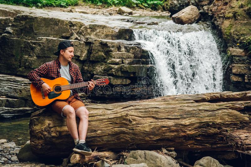 De mens speelt een gitaarzitting op een boomstam van een boom tegen een waterval Ruimte voor uw sms-bericht of promotieinhoud royalty-vrije stock foto's