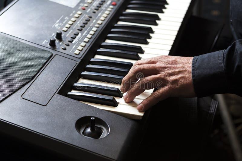 De mens speelt de piano met zijn handen royalty-vrije stock afbeelding
