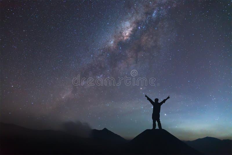 De mens spreidt hand op heuvel uit en ziet de Melkweg royalty-vrije stock afbeelding