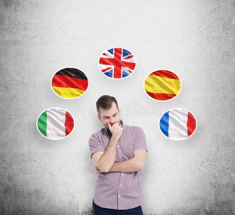 De mens in toevallig overhemd houdt zijn kin en denkt over welke taal aan studie Italiaans, Duits, het Verenigd Koninkrijk, Spaan royalty-vrije stock foto