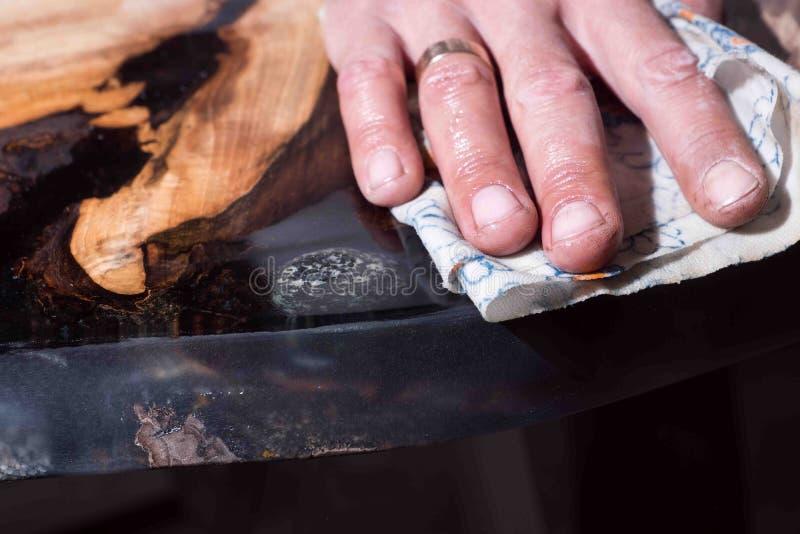 De mens toont het verschil natte boom en droog zwarte hars met binnen stenen stock foto's
