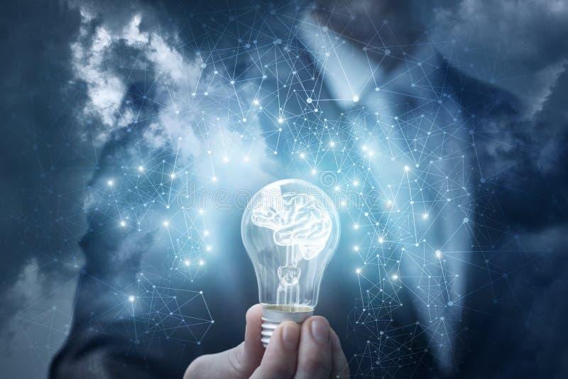 De mens toont de lamp met de hersenen in de hemel stock afbeelding