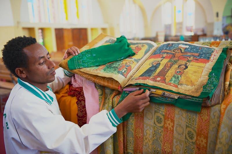 De mens toont oude Bijbel in Amharic-taal in de kerk van Onze Dame Mary van Zion, de heiligste plaats voor Orthodox allen aan royalty-vrije stock afbeeldingen