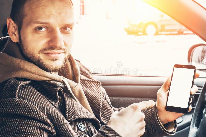 De mens toont vinger bij witte spot op de zitting van het telefoonscherm in auto stock foto's