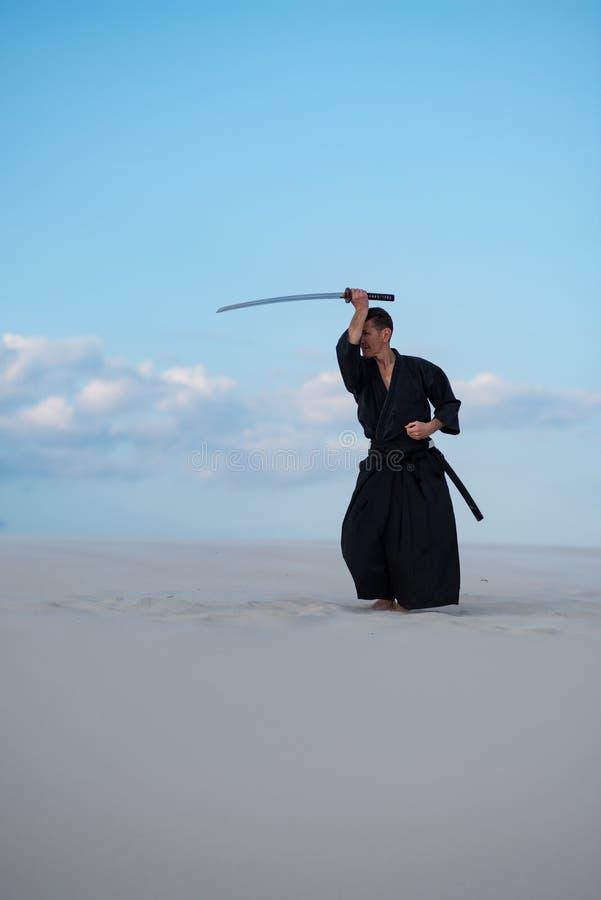 De mens, in traditionele Japanse kleren, oefent vechtsporten uit royalty-vrije stock foto