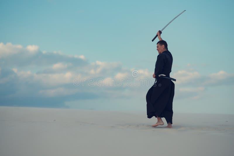 De mens, in traditionele Japanse kleren, oefent vechtsporten uit royalty-vrije stock afbeeldingen