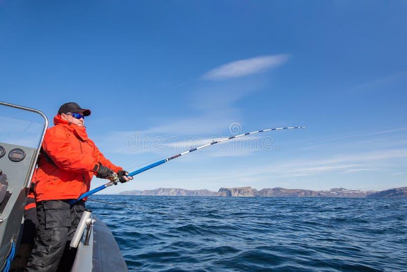 De mens trekt een vis uit water Rood jasje Sportenglazen Fishe stock afbeelding
