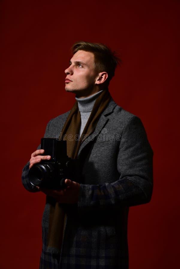 De mens in uitstekende stijl houdt digitale camera fotograaf stock foto