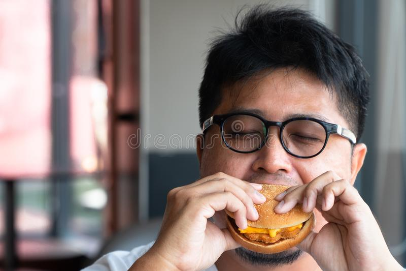 De mens van Azi? eet hamburger in een snel voedselrestaurant en geniet van heerlijk voedsel mens die in een Witte t-shirt en glaz stock fotografie