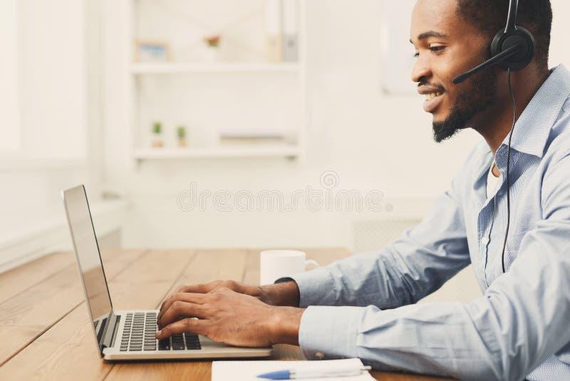 De mens van de call centreexploitant met hoofdtelefoon het werken stock afbeeldingen