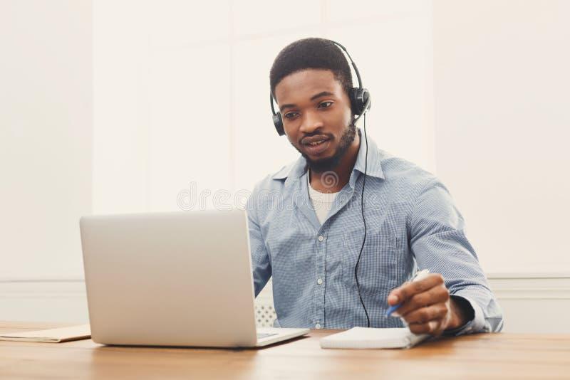 De mens van de call centreexploitant met hoofdtelefoon het werken stock afbeelding