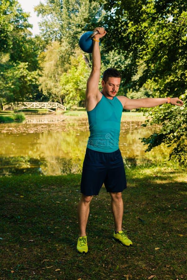 De mens van de Crossfitgeschiktheid opleiding met kettlebell in het park stock afbeeldingen